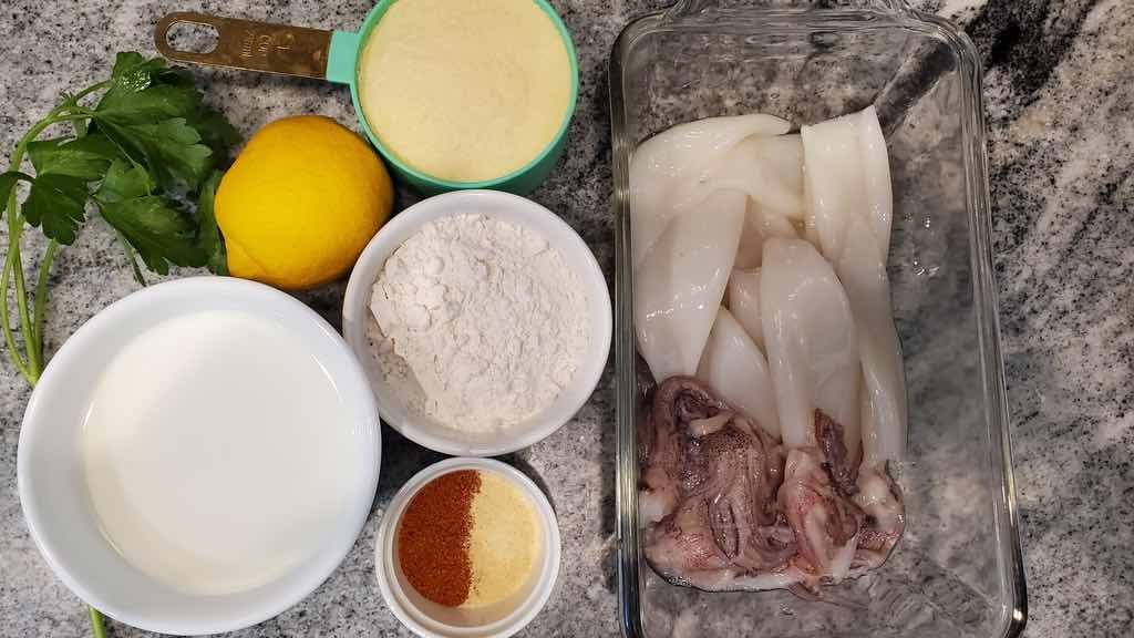The ingredients for making air fryer calamari include milk, lemon juice, squid tentacles and rings, flour, semolina flour, cornmeal, parsley, old bay seasoning, granulated garlic, salt and pepper.