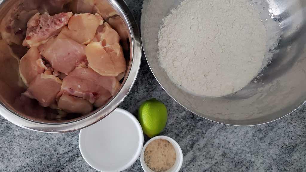 Ingredients for chicharron de pollo include bone-in chicken, flour, vinegar, adobo and lime juice.