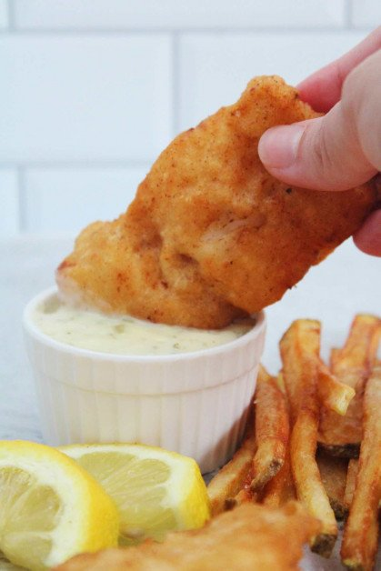 Fried fish being dipped into tartar sauce.