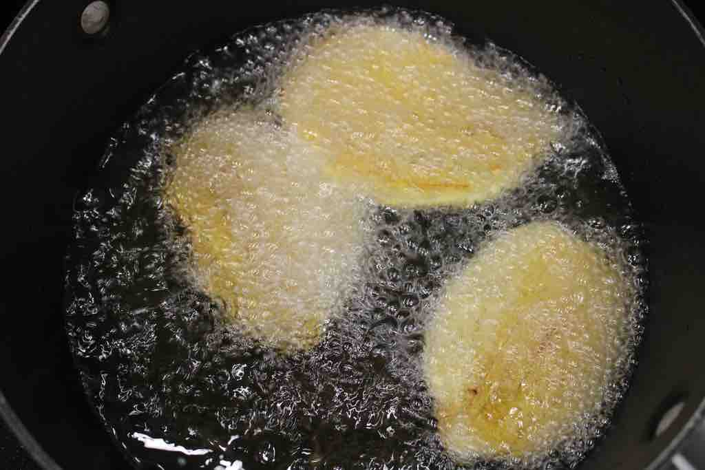 Smash the plantains between parchment paper using a cutting board and frying once again.
