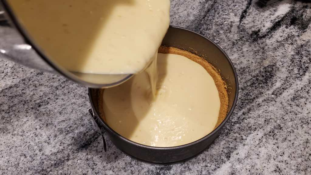 During the cheesecake filling into the crust.