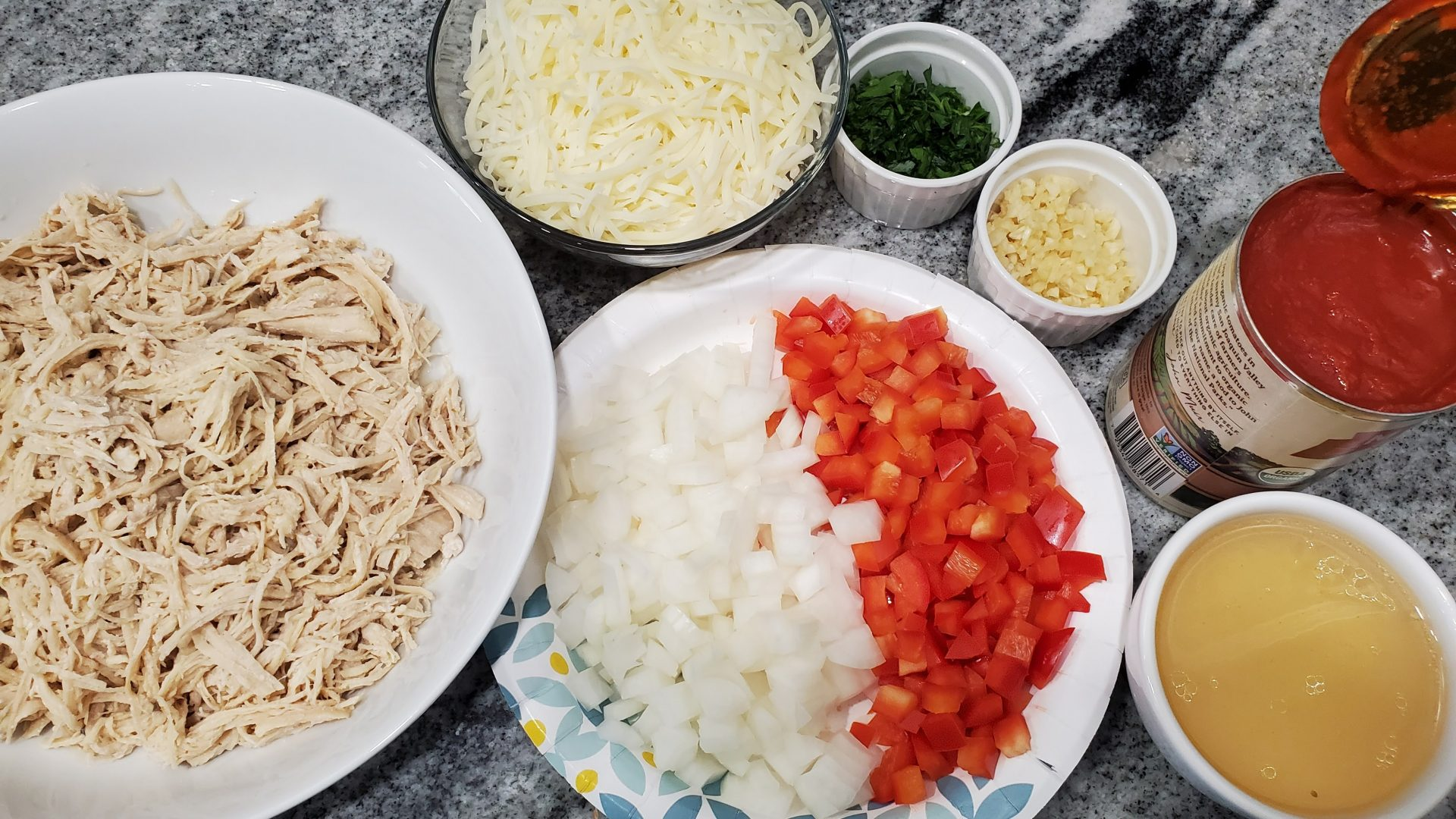 The ingredients needed to make a chicken lasagna are shredded chicken, cheese, red pepper, onion, garlic, tomato sauce, chicken broth, heavy cream and parsley.