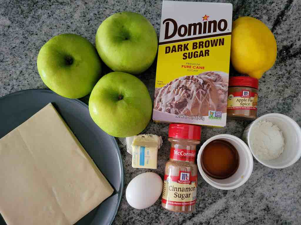 The ingredients needed are apples, egg roll wraps, cinnamon, vanilla extract, lemon juice, corn starch, egg, melted butter, cinnamon sugar, apple pie spice and brown sugar.