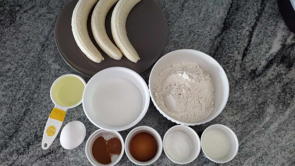 The ingredients needed to make air fried banana muffins are bananas, sugar, egg, vanilla extract, oil, milk, flour, baking powder, salt, cinnamon and nutmeg