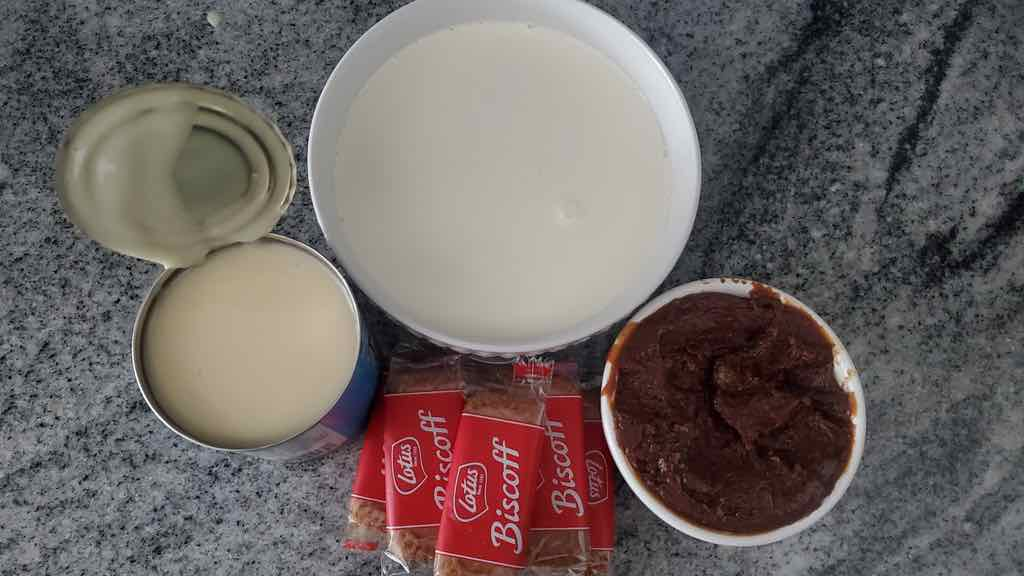 The ingredients needed are cookie spread, biscoff cookies, sweetened condensed milk and heavy cream.
