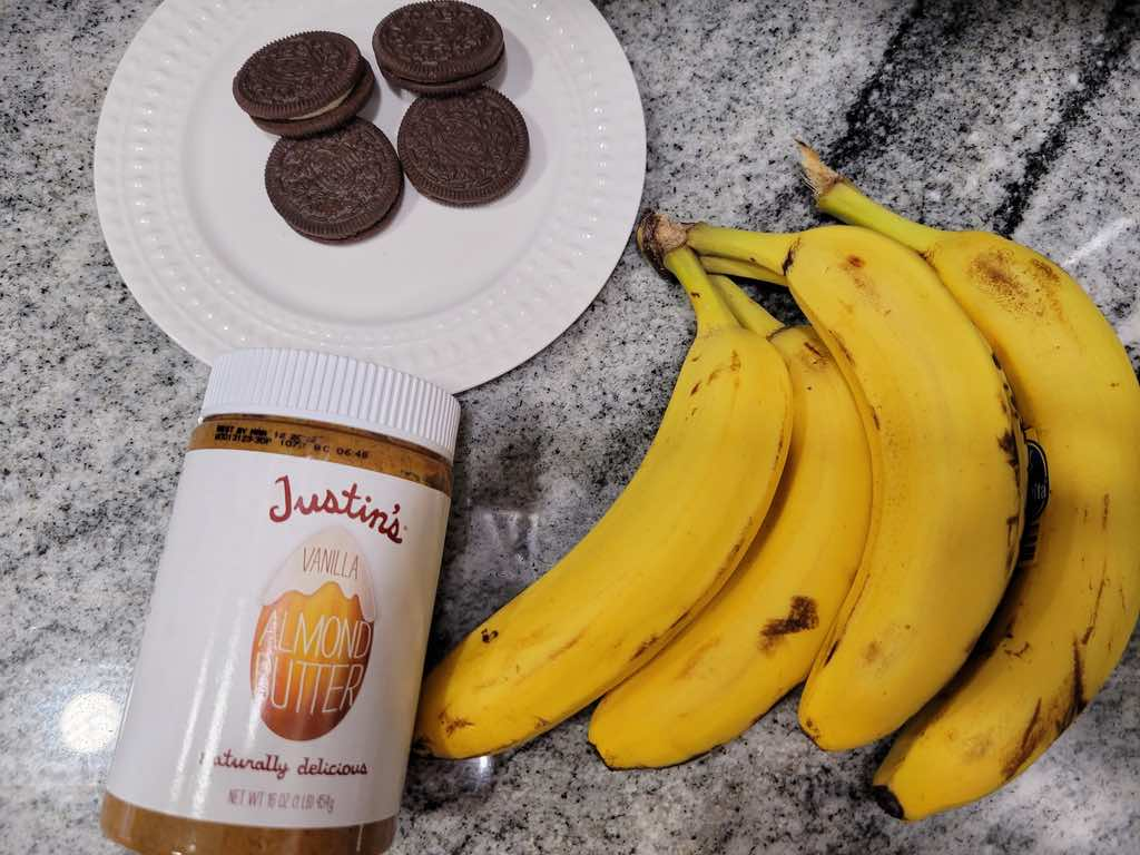 These are the ingredients needed to make cookies and cream nice cream, frozen bananas, vanilla almond butter and Oreos.