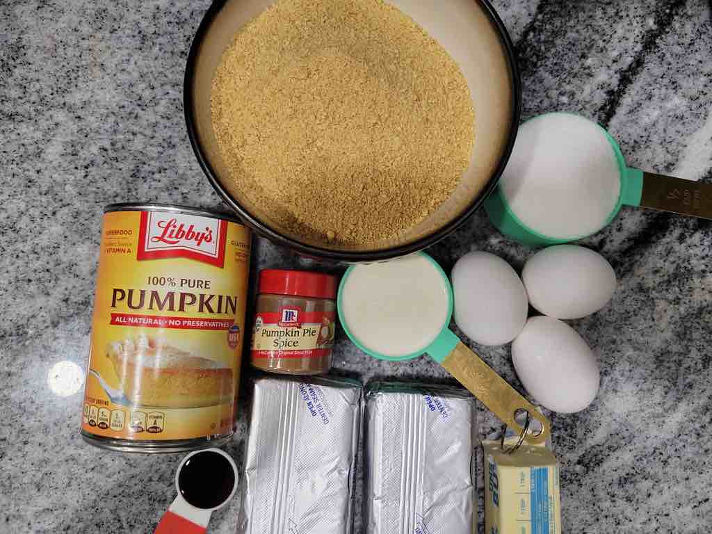 The ingredients needed for this recipe are cream cheese, heavy cream, pumpkin puree, pumpkin pie spice, eggs, vanilla extract, graham crackers, sugar, and butter.