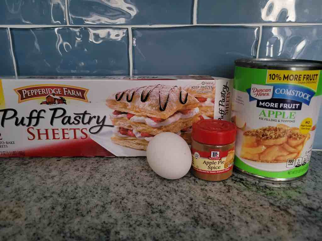 The ingredients needed are puff pastry sheets, canned apple pie filling, egg and apple pie spice.