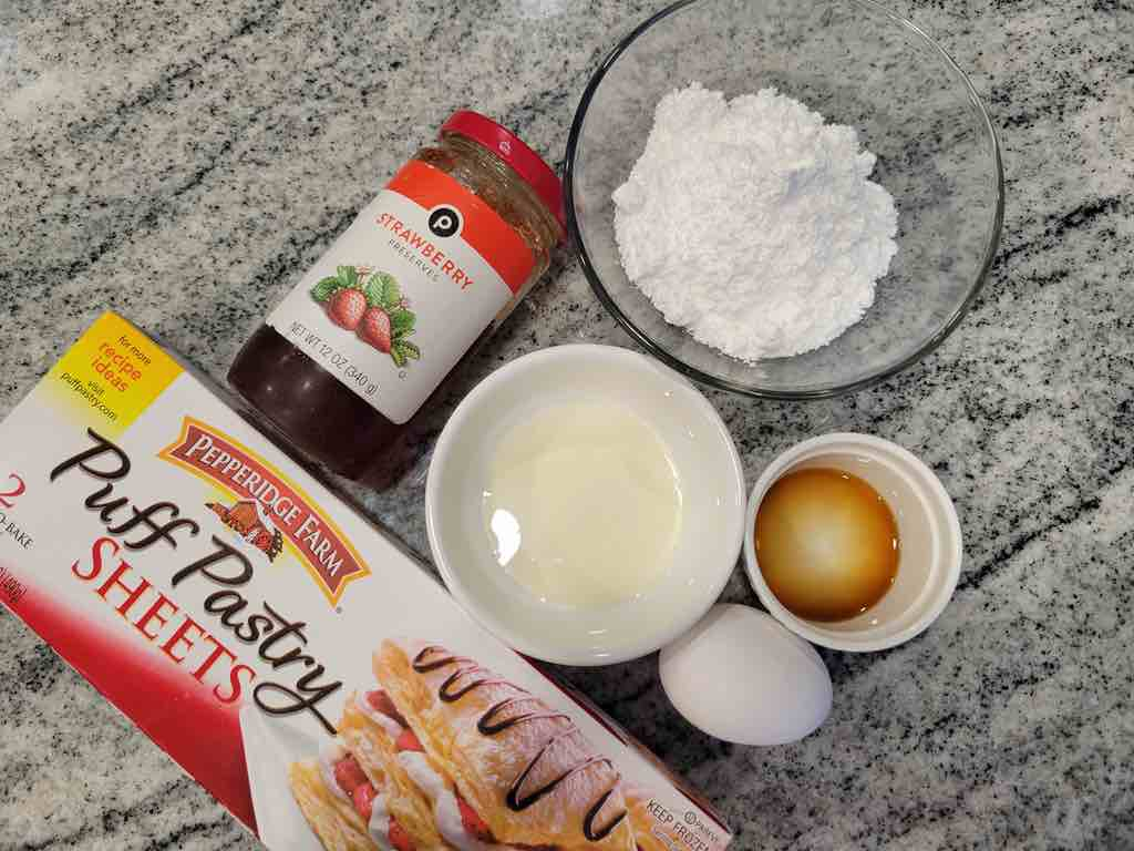 The ingredients needed are puff pastry sheets, strawberry preserves, egg, powdered sugar, vanilla extract and heavy cream.