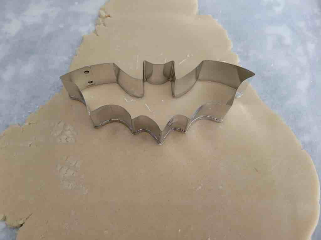 Use a bat shaped cookie cutter to cut out the cookies. Make sure to press down into the dough to form the shape as shown.