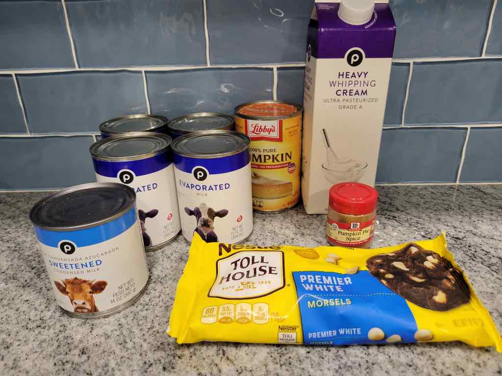 The ingredients needed are evaporated milk, heavy cream, sweetened condensed milk, pumpkin puree, pumpkin pie spice and white chocolate chips.