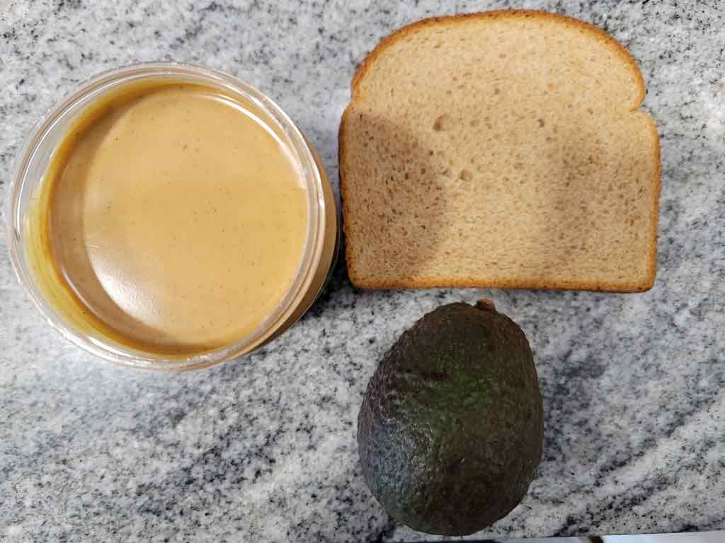 The ingredients needed are sliced bread, avocado and peanut butter.