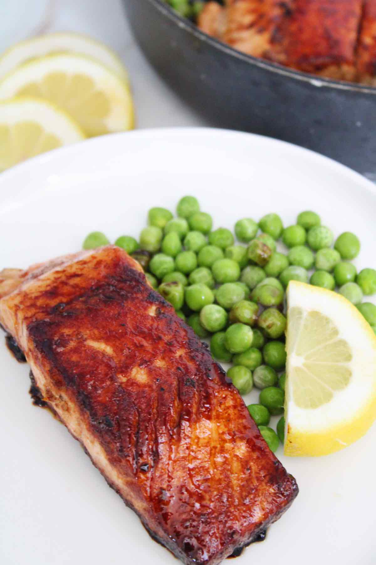 Pan seared salmon fillets served with peas and fresh lemons.